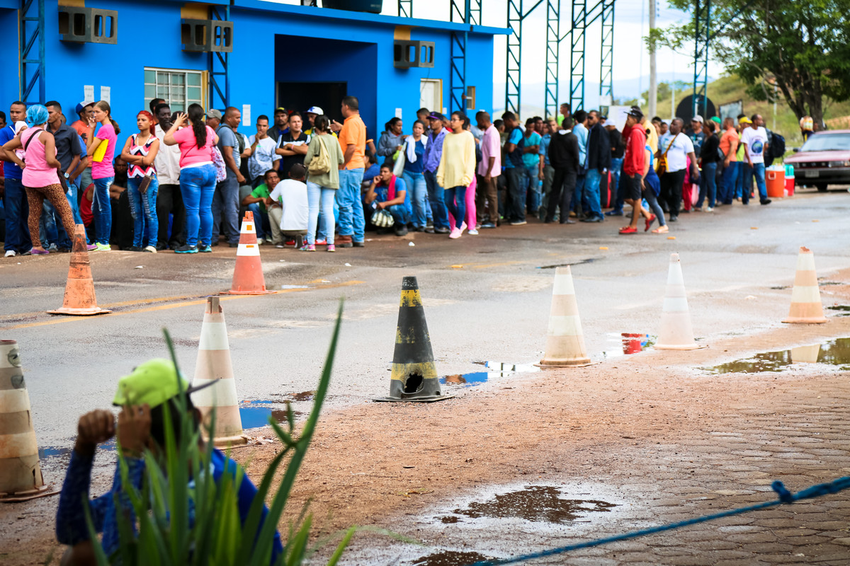 Migrantes venezuelanos fazem fila no posto de fronteira da Polícia Federal na cidade de Pacaraima (RR) para registrar a entrada no país (Foto: Leonardo Medeiros/Conectas - 2018)