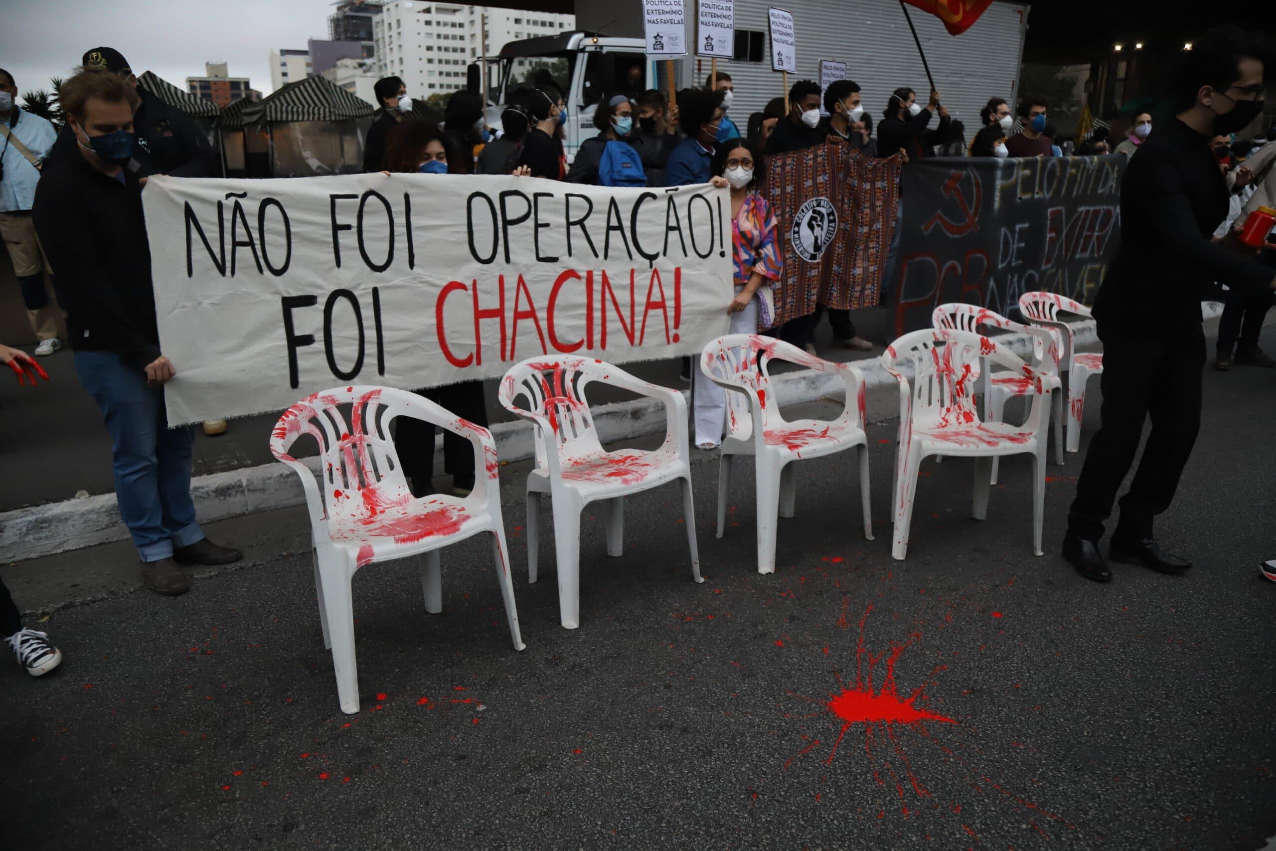Manifestantes pintam de vermelho quatro cadeiras simulando sangue. Atrás, uma faixa diz
